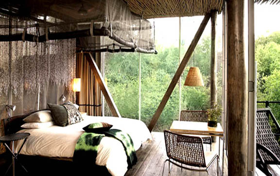 The beautiful bedroom and view that one can experience when they stay at the Sweni Lodges, Singita Lodges, South Africa.