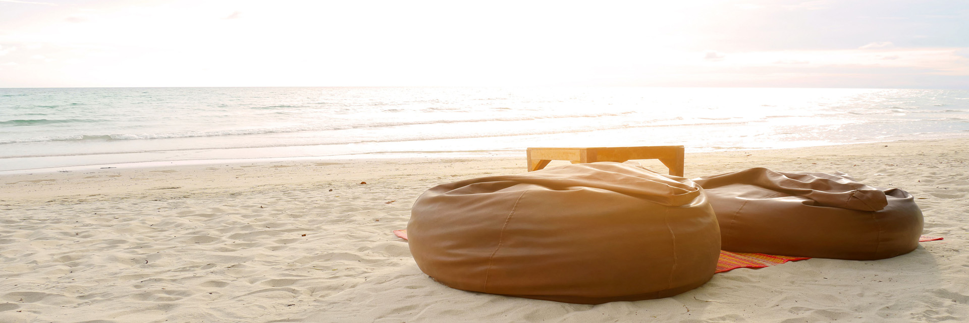 Bean bags and table set on the beach at sunset